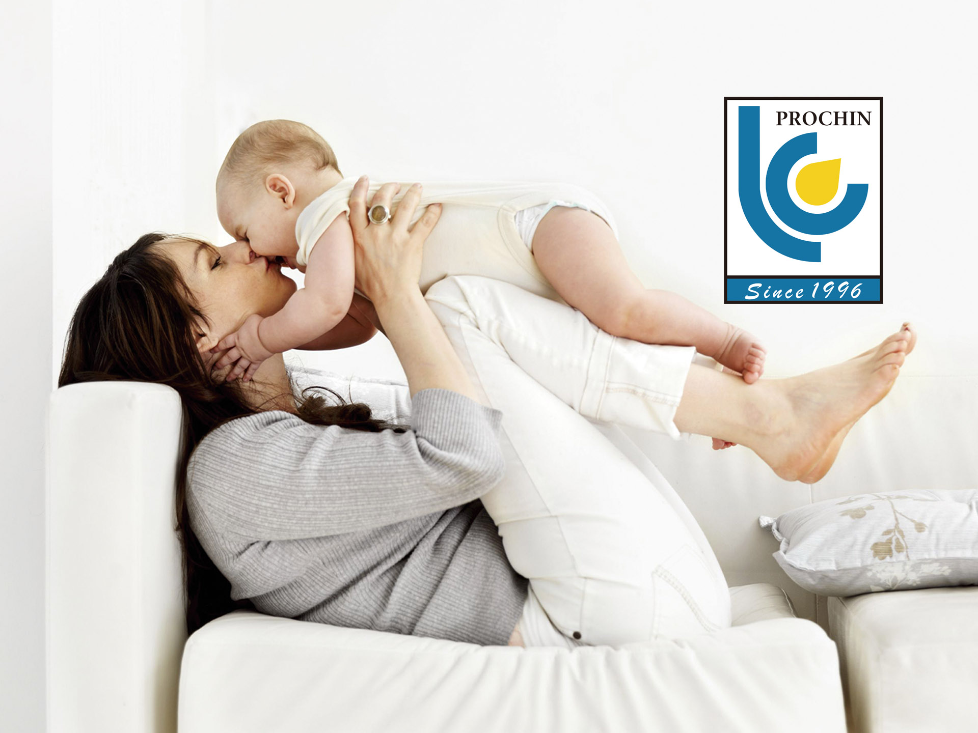 mom holding a baby on a white fresh sofa couch