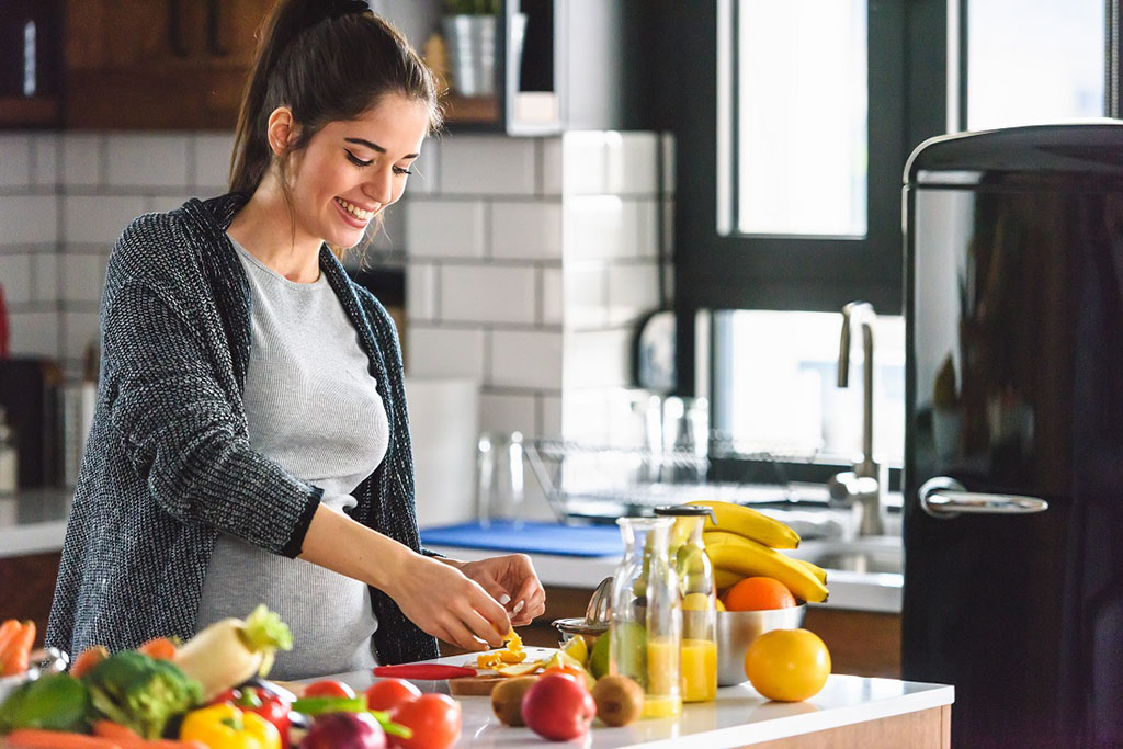 Beautiful smiling young pregnant woman preparing healthy food wi